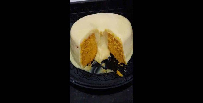 Cobrindo bolo vulcão de cenoura com cobertura de brigadeiro branco